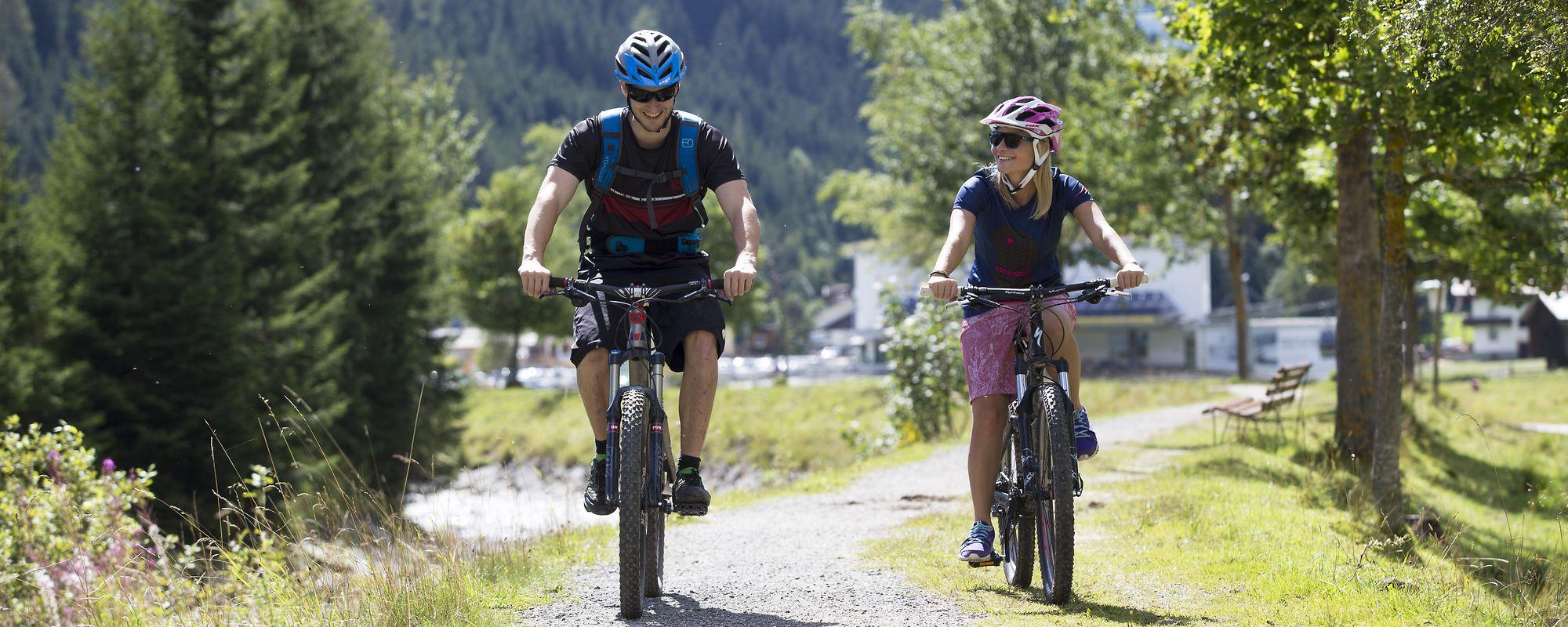 Mann und Frau unterwegs auf den Mountainbikes auf dem Radweg in Gerlos, Dorf im Hintergrund