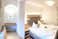 Panorama-Aufnahme des Doppelzimmers mit Blick auf Couch, Bett und Eingang im Apartment Edelweiss