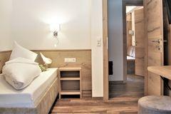 Blick auf das Single-Bett und die geöffnete Zimmertür im Einzelzimmer des Apartment Edelweiss