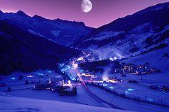 Spektakuläre Nachtaufnahme des tief verschneiten Winterdorfes Gerlos mit violetter Lichtstimmung und bei Vollmond