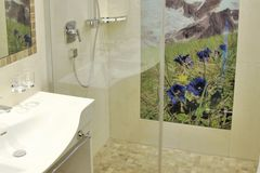 Badezimmer im Apartment Enzian mit großer, barrierefreier Dusche und Doppelwaschbecken