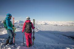 Paar mit Skiern in der Hand blickt auf die Nebeldecke über dem Talboden, bereit zur Abfahrt über die Pisten