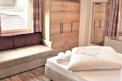 Blick vom Doppelbett auf die Couch und den Schrank im Doppelzimmer des Apartment Almrose
