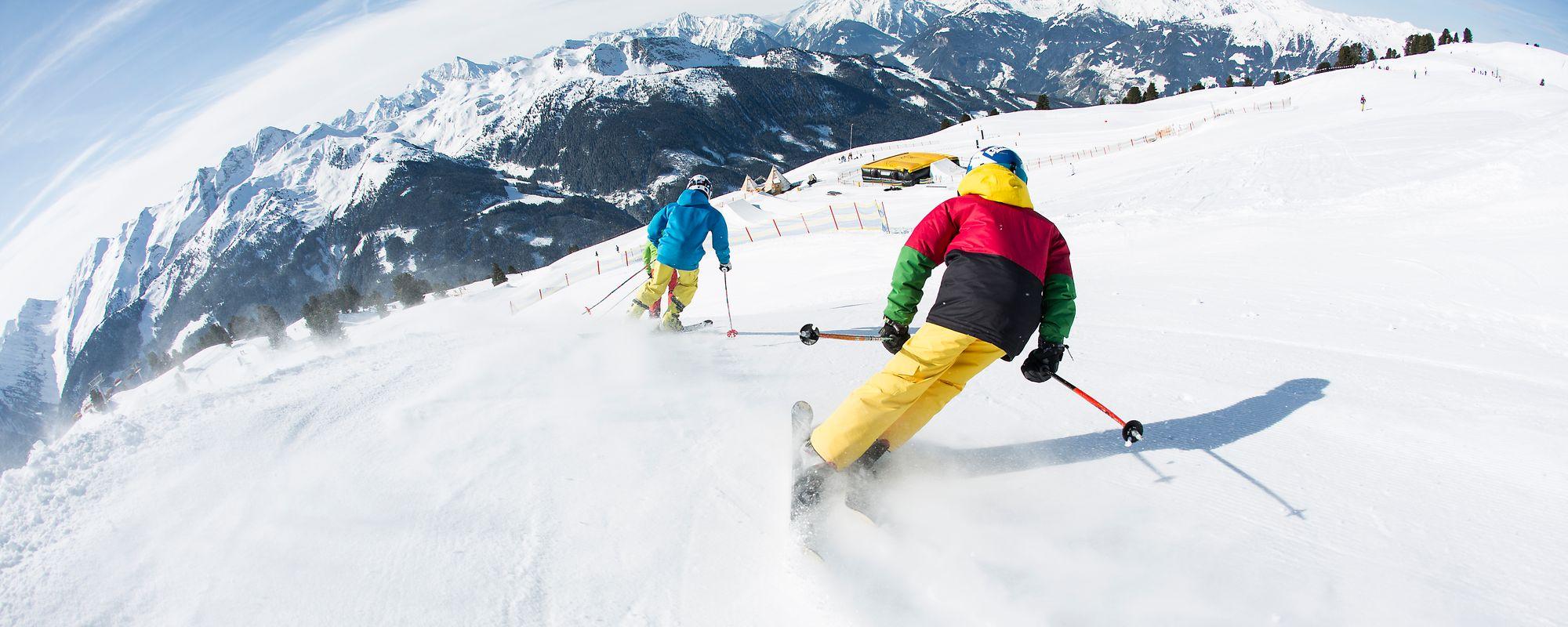 Skifahrer carven im Actionpark Kreuzwiese durch den Schnee, fotografiert von hinten
