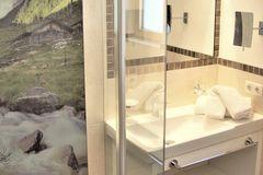 Badezimmer mit barrierefreier Dusche, großem Waschbecken und Spiegel