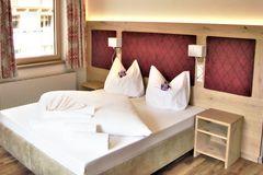 Blick auf das frisch gemachte Bett mit Holzvertäfelung und Designelement am Kopfteil