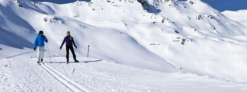 Paar beim Langlaufen auf der Höhenloipe in Gerlos, ringsum tief verschneite Berge und Hänge