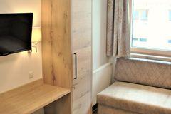 Schreibtisch, Schrank und Couch im Einzelzimmer des Apartment Edelweiss