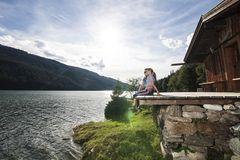 Verliebtes Paar sitzt beim Sonnenuntergang am Steg bei einer Hütte am Durlassboden Stausee